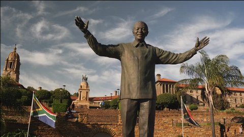 Pretoria, South Africa - circa January 2019: Statue of Nelson Mandela in the gardens of Union Buildings, government offices in capital city, with South African flag flying in wind on sunny day, jib up