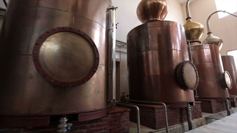 Large stainless steel brandy distilling tanks. Silos for wine and cognac fermentation . Steel barrels for fermentation of wine in winemaker factory . Dolly , ronin movement a long row of spirit vats .