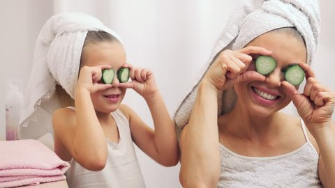 Wellness, spa, skincare concept. Young woman with daughter putting cucumbers on eyes, having fun after bath.