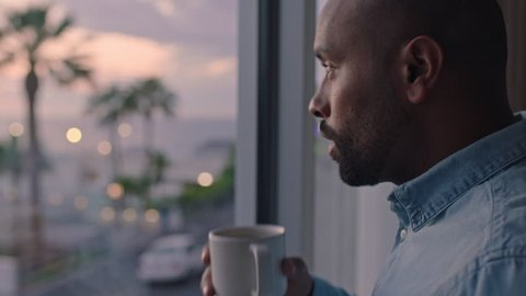 attractive man drinking coffee looking out window in hotel room enjoying early morning view at sunrise contemplating future planning ahead
