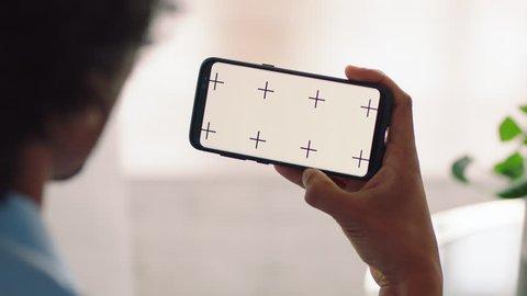 man using smartphone green screen video chatting watching online entertainment enjoying mobile communication on chroma key display horizontal orientation
