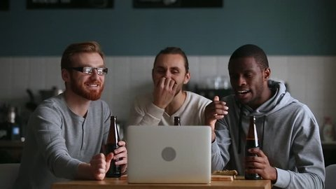Millennial guys friends buddies male football fans supporters watching online game on laptop hanging in pub drink beer cheering sport soccer winning team celebrating goal excited by victory score