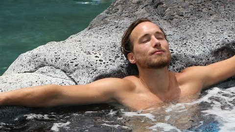 Spa wellness - man relaxing in hot tub outdoor at luxury resort spa retreat. Happy young male model relaxed resting in water on vacation travel holidays.