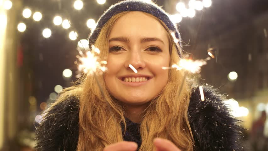 Portrait of smilling pretty woman with sparklers in hands close up. Sparks scatters in different directions | Shutterstock HD Video #1022388388