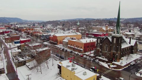 A snowy winter reverse aerial view of the business district of a typical Pennsylvania rust belt river town at Christmastime. Pittsburgh suburbs.