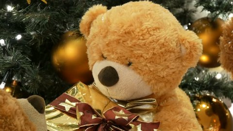 Funny brown moving teddy bears that hold a box with a gift in their paws. Christmas decorations in the mall