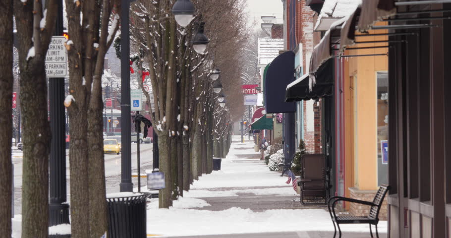 A long shot of a man salting the sidewalk outside a business during a snowstorm. Non-snowing version.  | Shutterstock HD Video #1022398768
