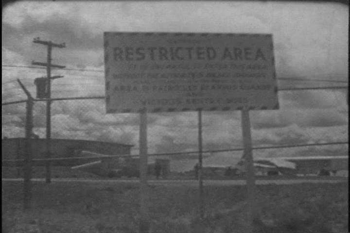 CIRCA 1960s - A Strategic Air Command pilot visits his wife in their car at a restricted area and pilots exit a BX.