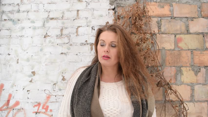 Young fat woman in the dry branches on the background of old brick wall in  winter