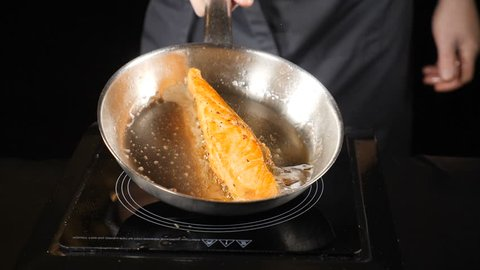 Unhealthy fat food concept. Pan-fried Salmon, trout. Salmon fillet skin side down on the pan. Slices of red fish fried in a pan. Chef pouring oil with a spoon. hd . Slow motion.