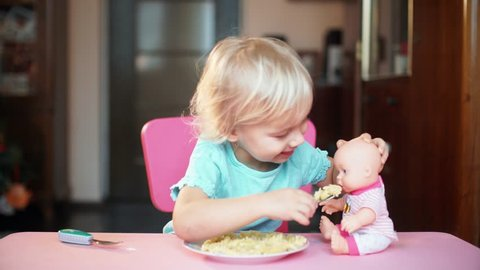 Adorable baby girl eating from fork vegetables and pasta. Little child feeding and playing with toy doll
