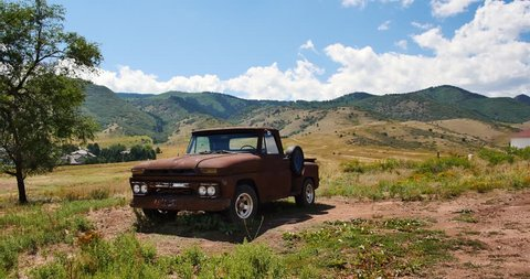 Handheld shot of vintage pickup truck parked in the mountains