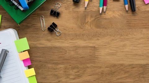 Notebook and colorful stationery on wood table with copy space for education background concept, top view