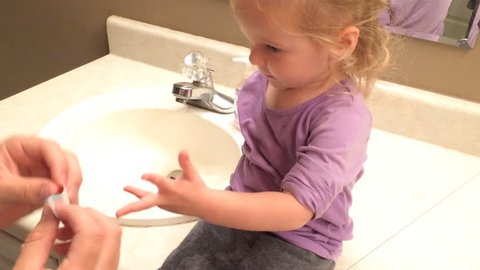 Dad putting band aid on little girls finger in bathroom
