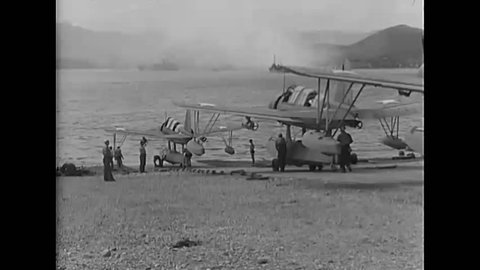 CIRCA 1940s - Vought OS2U Kingfisher floatplanes move down a ramp and taxi across a harbor and a pilot is shown in the cockpit of a warplane.