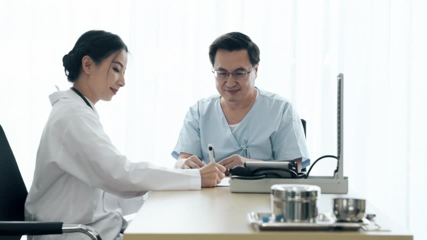 Doctor with patient. Young female medical doctor talking to a senior patient at hospital. Taking notes. Senior care medical and insurance concept. | Shutterstock HD Video #1022583418