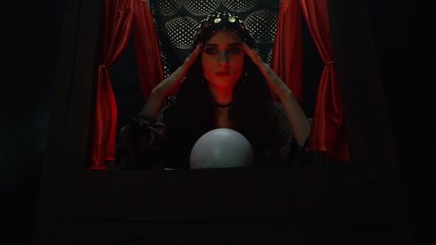 A witch tells fortunes, concentrating and using a crystal ball