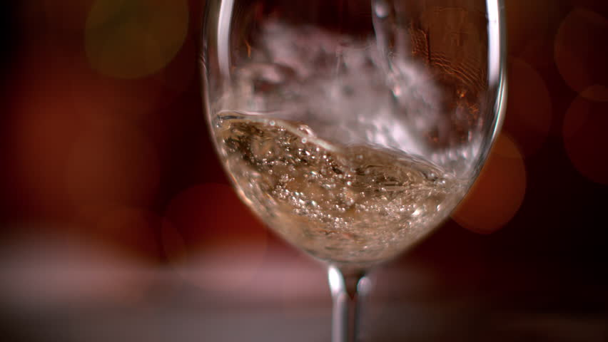 Super slow motion of pouring white wine into glass. Filmed on high speed cinema camera, 1000 fps.