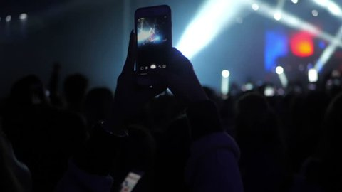 People taking video and photos on mobile smart phone at concert party crowd