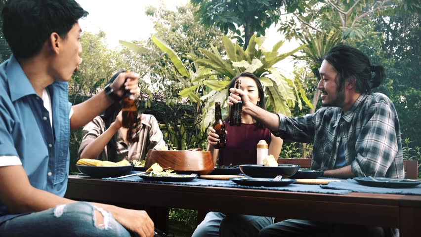 Friends enjoying outdoor food together. Group of Asian, chinese, thai friends having dinner together with beer, toasting action. House party concept. | Shutterstock HD Video #1022637118