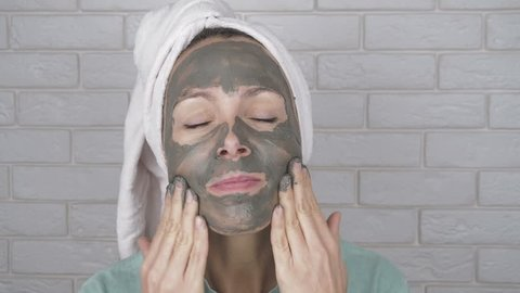 Beauty procedures. Attractive woman applying face mask. Head wrapped in towel.