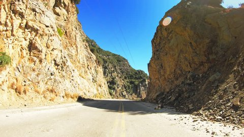 Car travel gopro point of view across mediterranean coastline nature, steep rocky slopes and sunny blue sky, asphalt road POV drive