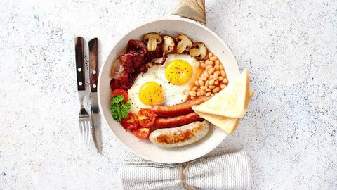 Full English Breakfast served in a pan. Fried eggs, beked beans, tomatoes, champignons, crispy bacon, sausages and toast. Placed on stone background. Top view with copy space.