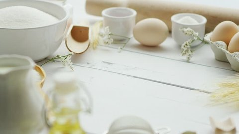 Assorted ingredients for pastry preparation and cooking tools lying in circle on white timber tabletop