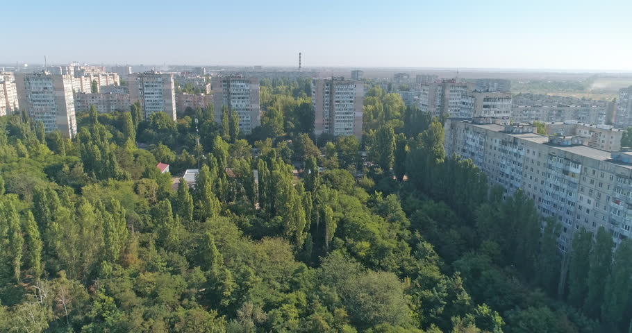 Aerial view city covered with trees and building in Soviet architectural style