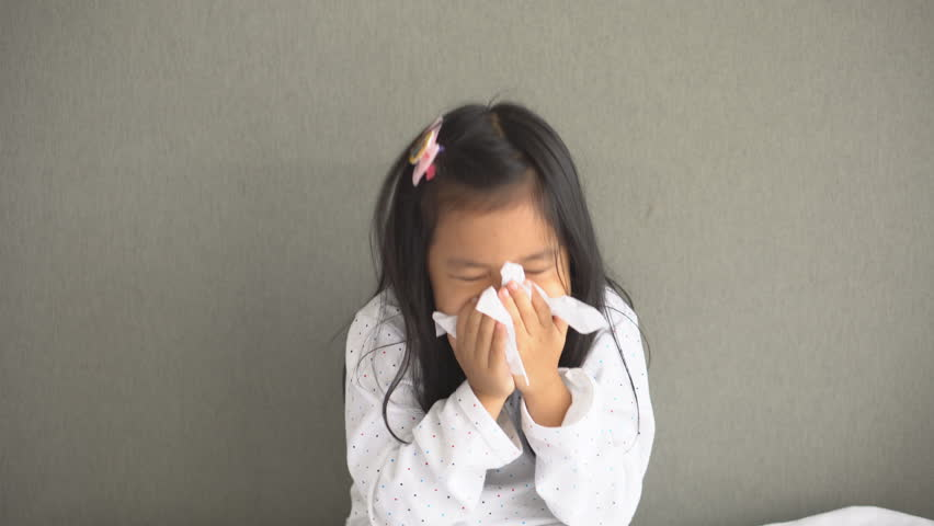 Asian child or kid girl sick with sneezing on nose and cold cough on tissue paper because weak or virus and bacteria from dust weather and kindergarten and pre school for medical background gray space | Shutterstock HD Video #1022690188