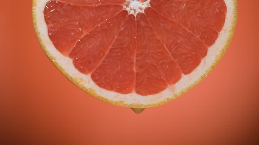Closeup juice droplets flowing in glass from grapefruit or red sicilian orange #1022702968