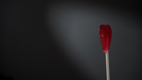 Sweet candy red heart on stick rotating against dark background. Love, valentines day or charity concept