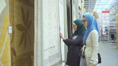 Two arab young women in hijab choose carpet