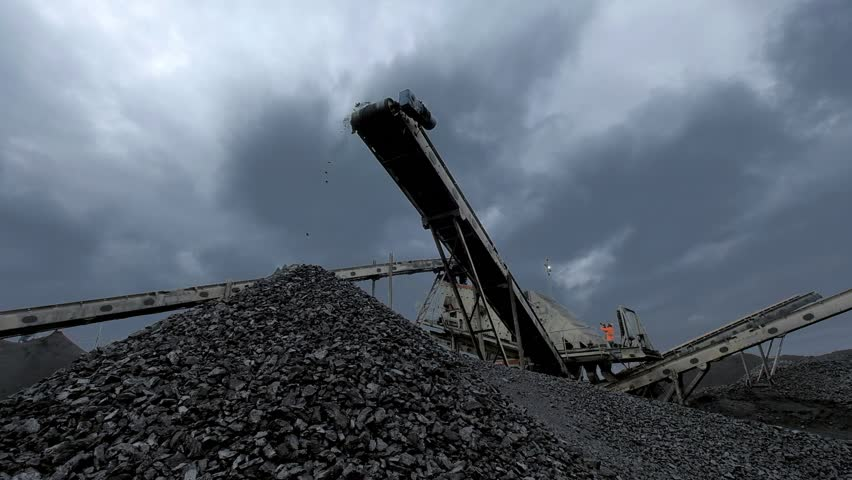 An overview of coal falling from the moving belt conveyor into the huge pile at the coal mine with coal miners working on the background | Shutterstock HD Video #1022731078