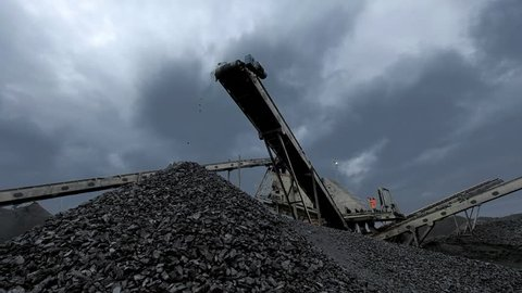 An overview of coal falling from the moving belt conveyor into the huge pile at the coal mine with coal miners working on the background