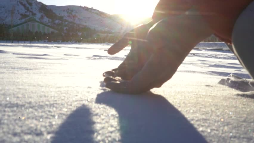 hands in the snow against a background of mountains in the winter in the wind #1022764048