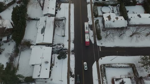 Aerial footage looking down at a bus and rising whilst following a car down the Main Street of a small town in the winter towards a sunset.