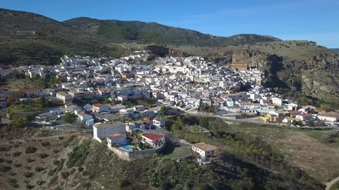 Aerial view of a traditional spanish white village in the mountains with a big chuch.
