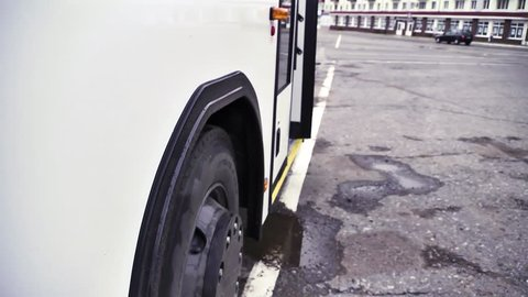 Side view of the white bus with bus wheel starting to move on grey asphalt background. Scene. Close up of white passenger bus and its wheel beginning to go, commercial transport wheels concept.