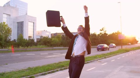 SLOW MOTION, SUN FLARE, CLOSE UP: Excited Caucasian yuppie dancing down the sunlit street after getting promoted. Happy businessman dances along the empty sidewalk on a beautiful summer evening.