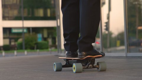 CLOSE UP: Unrecognizable man going home from work on his electric skateboard. Young businessman in a suit cruising through the city on his longboard. Active manager going to meeting on skateboard