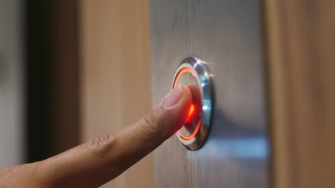 Female Hand Pushing Elevator Button in Office Center or Hotel. Young Woman Pressing Lift Button Down. 4K Slowmotion.