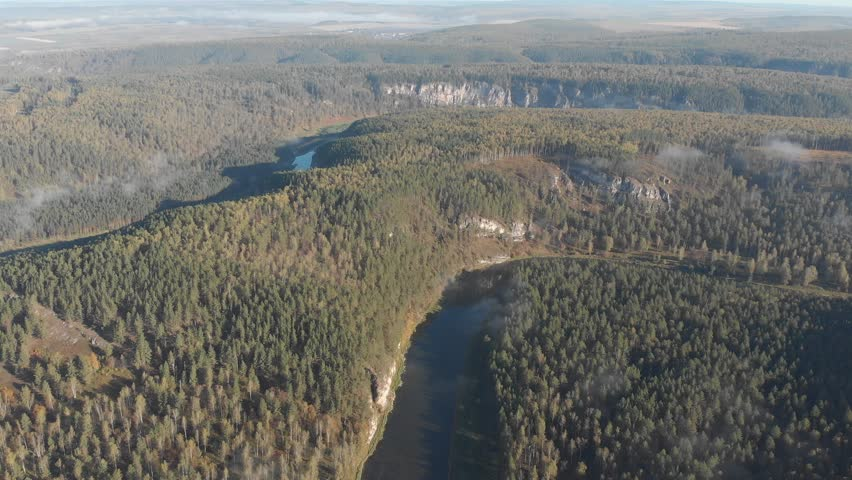 Slow aerial flight backwards over a gentle mountain river, pine forest, clouds. | Shutterstock HD Video #1022855548