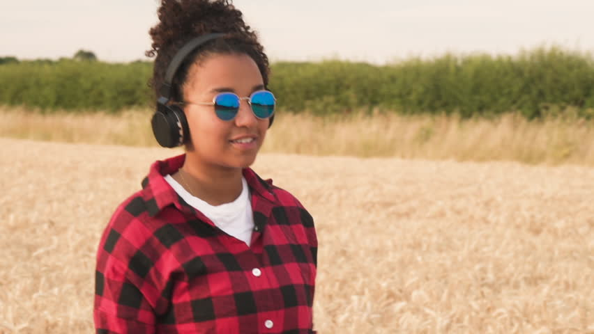 Slow motion tracking video of beautiful mixed race African American girl teenager young woman walking in a field, wearing a blue sunglasses listening to music on her cell phone and wirele
