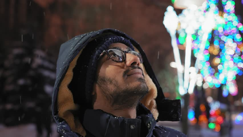 Close-up, Indian Guy Looks Up at Flying Snow in the Evening in the Park | Shutterstock HD Video #1022896828
