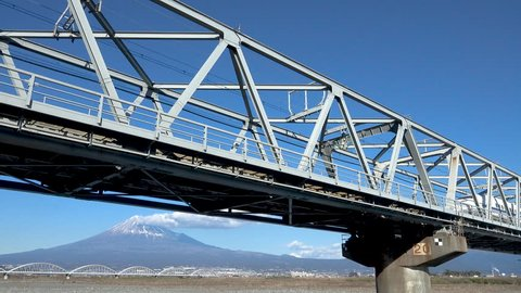 Shinkansen bullet train passing through Mount Fuji and the Fujikawa bridge, Shizuoka. Japan