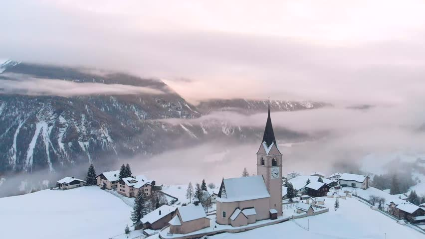 Winter top view of the Swiss village with a church, fog and clouds in the mountains in the Alps, snow-covered houses in the valley of mountains and lakes, flying above the clouds and sunset.