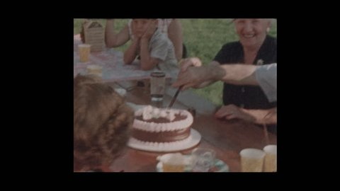1956 Elderly couple slices and shares anniversary cake and kiss