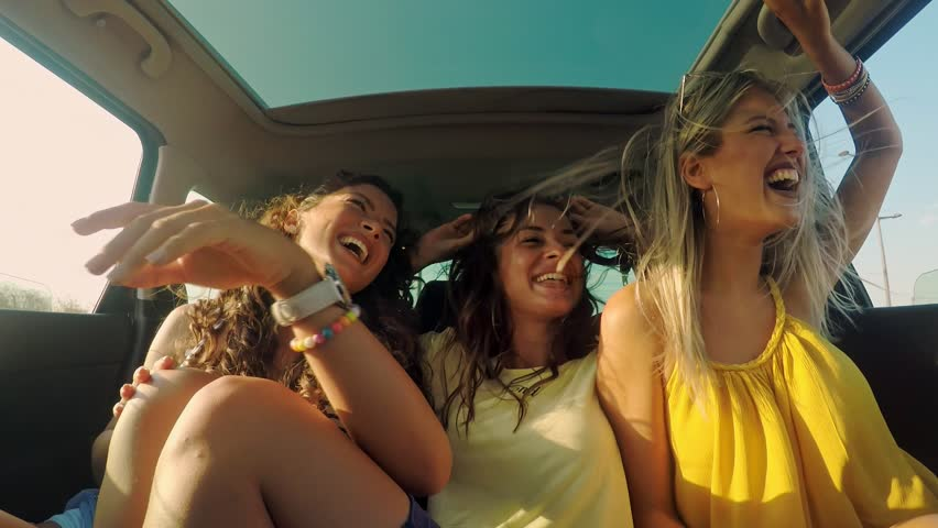 Three female friends enjoying traveling in the car. Sitting in rear seat and having fun on a road trip. | Shutterstock HD Video #1022988568