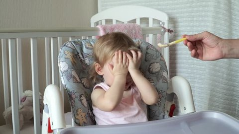 The little girl does not want to eat baby food, and covers her face with her hands
